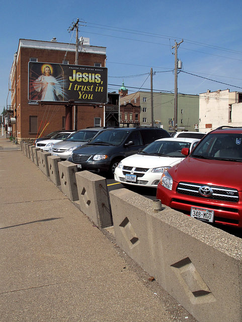 A sidewalk/parking lot boundary wall idea that Jesus Christ came up with in Dubuque.  It was not a person that did that.