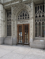 Brown-papered doors of the famous R. Morris bldg with its 4 little entryway heads.