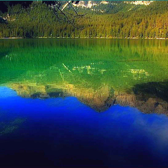 Sky, forest and mountains in the water.