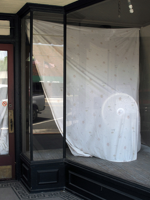 Art installation in storefront display window, of oscillating fans and bedsheets and pigtail fluorescents.