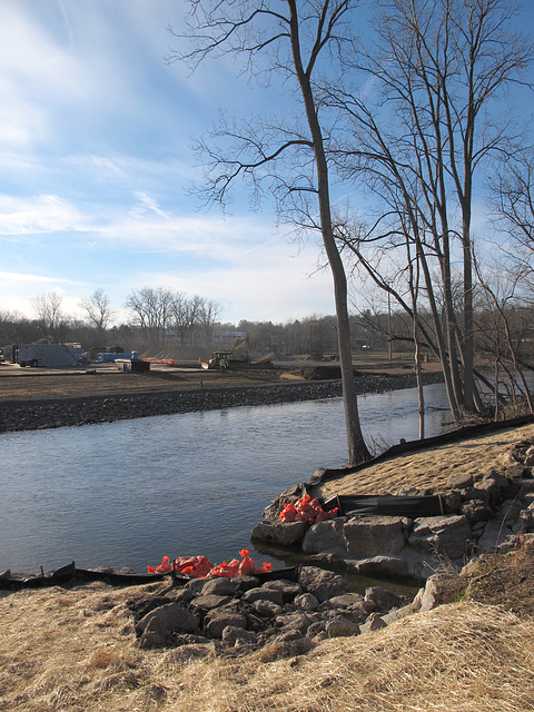 The Huron River among its silt fences and straw mats and riprap and orange sandbags.