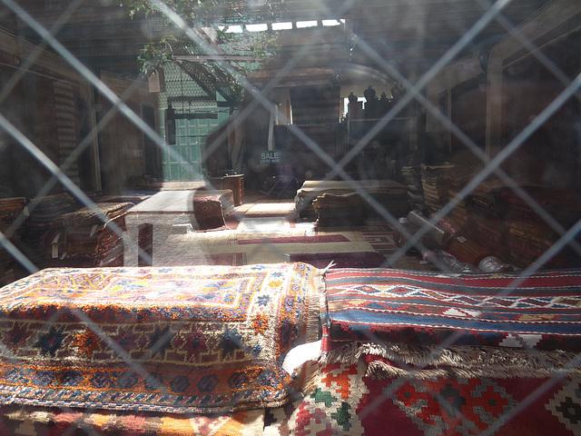 through the window of a rug shop