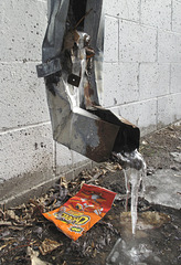 Up above the sack of Cheetos, a mangled downspout's got icicles.