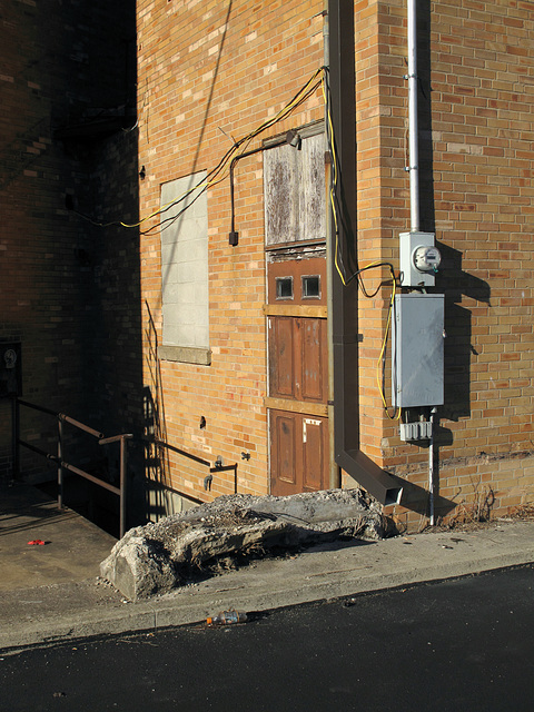 Barricaded door and heavy slab of petrified wood, among cinderblocked-up window and big long downspout and some other objects and surfaces such as cords and shadows.
