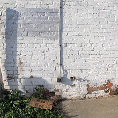 Outdoor electrical outlet with small spigot; cardboard box; and silver antigraffiti.