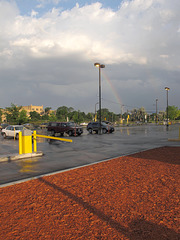 Wet parking; squishy carpet of vivid red mulch; yellow parking arm; rainbow.