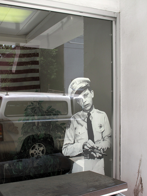 A cardboard cutout of a black-and-white Don Knotts, preparing an infliction of gun violence onto somebody.