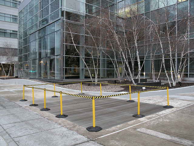 A giant grate that has to be monitored for signs of slipperiness everytime there's a slight change of weather condition, in the middle of a sidewalk in downtown Minneapolis.