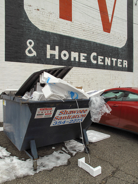 Shawnee Sanitation overflowing dumpster of styrofoam forms, at a TV & Home Center.