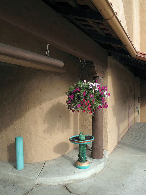 "A vertical-clearance rod and a basket of petunias each hang from hooks; a ""cactus-wearing-a-sombrero"" birdbath is filled up with potting soil."