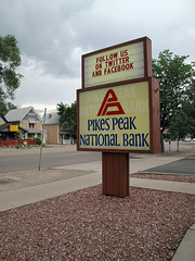 "PIKeS PeaK NaTIOnaL BanK triangular mountaintop logo, with visible ghost of the bank's former ""teeter totter"" logo layout.  Also imperative sentence of facebook-twitter."