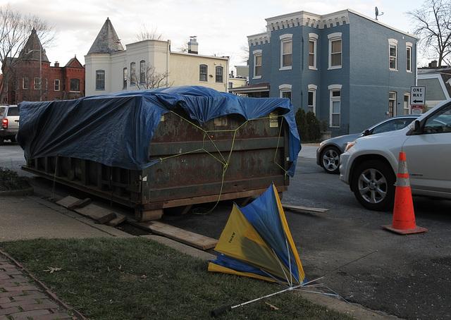 Washington DC street scene of dumpster tarpaulin and Ikea umbrella, amid residential.
