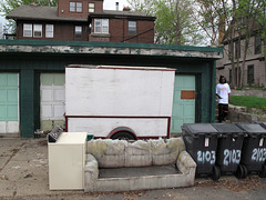 A gnawed-at old wet sofa is pressed in between an off-white clothes dryer and a lineup of roly 2103 garbages.  Two doors' worth of a lineup of green garages are blocked by a roly wooden trailer.  A man descends an outdoor staircase.