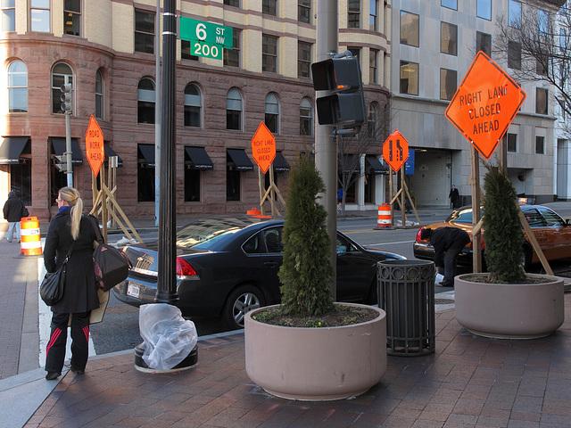 Orange warnings upon a streetscape.
