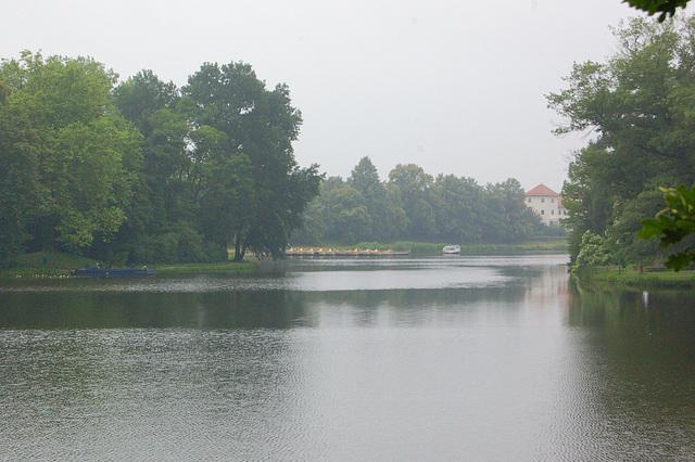 """Lago de Vorlico kun gondolstacio kaj restoracio """"Je la kverkokrono"""" (Wörlitzer See mit Gondelstation und Restaurant """"Zum Eichenkranz"""")"""