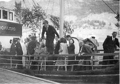(078) Brudeparet Hilma (Svendsen) og Signold Solem, 16. august 1950. Saudafjord legger til kai ved Sjøtun. Brudgommen (t.v.) og Magnus Kroken (nr. 2, f.h.) følger nøye med. Jens Bergum (på rekka) hopper i land.