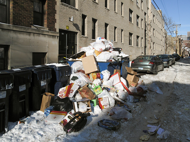 Massive overflow of a dumpster into a cold and snowy Minneapolis backalley.