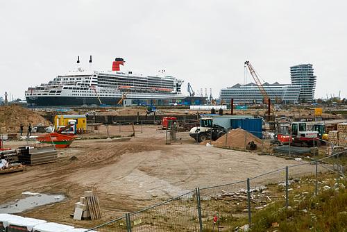 Baustelle an der Überseeallee mit Queen Mary 2 im Hintergrund