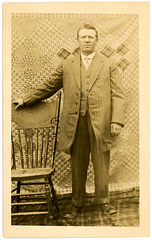 A Man Posing with a Chair, Quilt, and Blanket