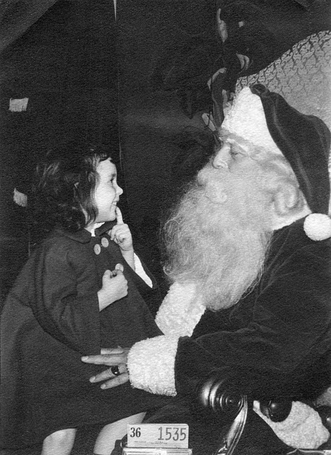 Is she showing Santa that she lost a tooth?