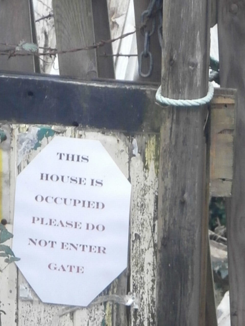 A sign pinned on the gate of the old house.