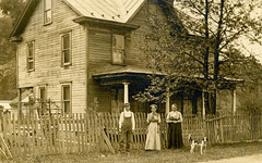 Boy, Women, and Dog in Front of a House
