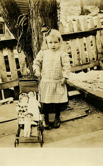 A Girl with a Baby Carriage Full of Dolls