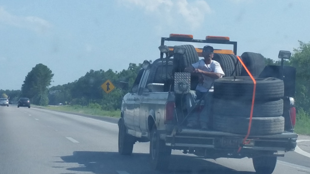 guy chilling out on back of truck on highway