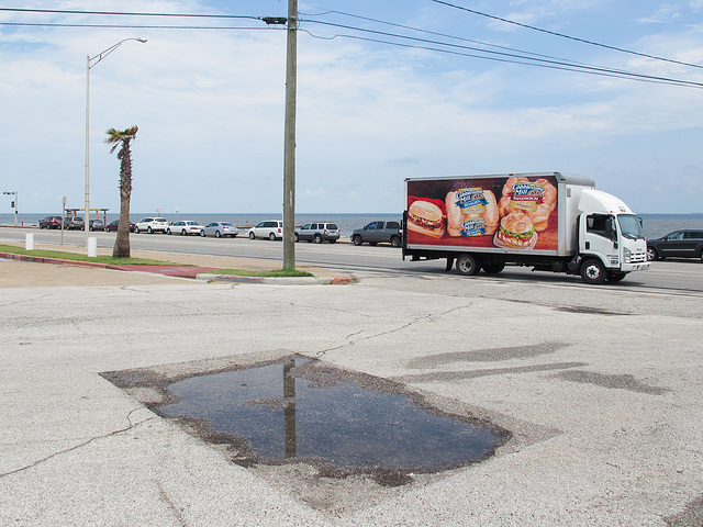 On the seashore, a rectangle of water as a truck of buns passes.