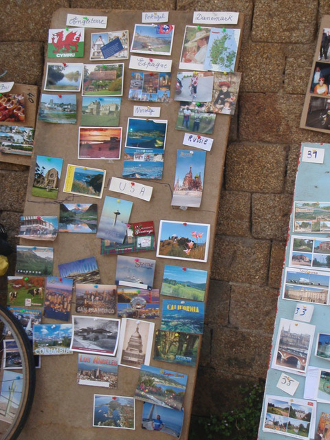 """Board with postcards at the La Tanniére crepe stop. The post cards are """"thank yous"""" from all over the world sent by past PBP riders after they returned home"""