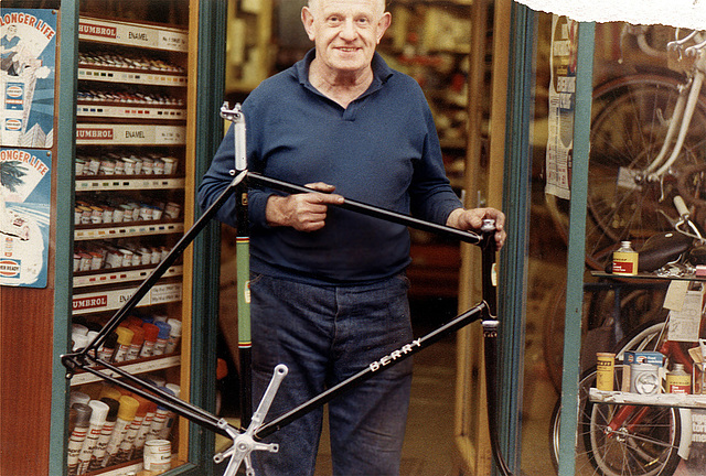 No. 721891 Delivery Day Johnny Berry holding frame in front of his shop, 5/72