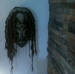 The mask clings to the wall...