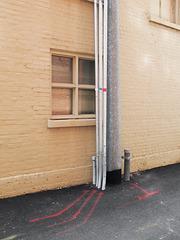 Red stripes, steel pipes, venetian blinds, painted bricks, blacktop.