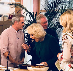 QUEEN CAMILLA WOLFS DOWN A PLATE OF GARLIC ESCARGOT WHILE THE HUSBAND ACTS AS A COVER.