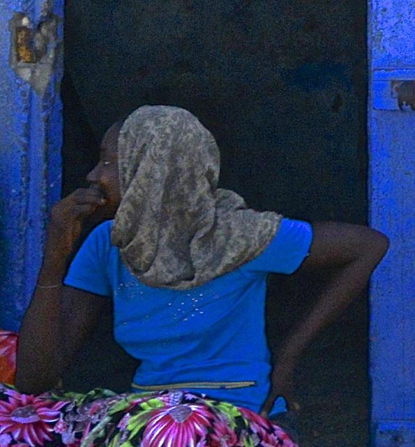 Jeune femme en bleu sur mur bleu