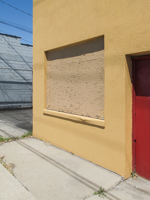 Tan-painted OSB for a golden-painted building with a red door.