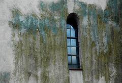 Schmales Fenster in grünlicher Wand