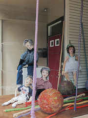 Fashion gallery of fully-clothed papier-mâché people with yarn crafts.