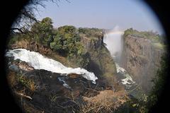 Rivero Zambezi, ravino... Dekstre, ĝuste sur la krutaĵo, sub la arboj, videblas blankaj punktetoj: estas homoj