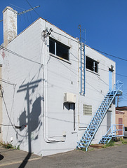 Commercial bldg with blue staircases, blue ladder, chimney, and antenna.
