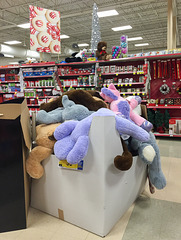 Huge cardboard box of plush animal toys for sale at a grocery store.