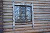Окно с решеткой и наличником в деревянном здании