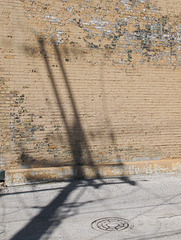 Enjoyment of shadows cast by utility poles onto walls of paint peeling from bricks.