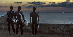 Surfers a la puesta de sol