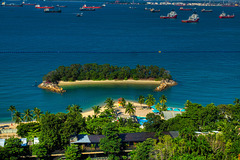 Beach on Sentosa island with ships in the roadstead in Singapore