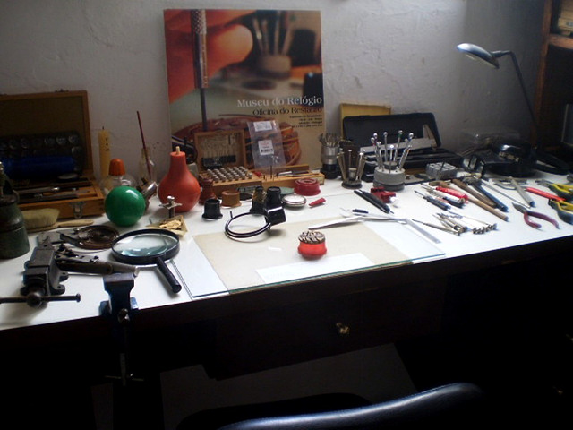 Table with equipment to restore and repair watches and clocks.
