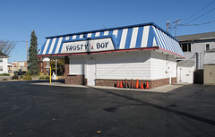 A smiling walking frosty boy has a cone, and a building has a lineup of cones.