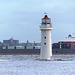 Perch rock lighthouse with the River Mersey ..Liverpool docks in the background.