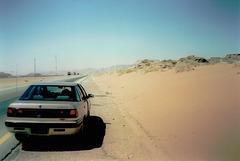 Asphalt, sand and trucks.