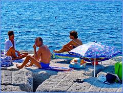 Spiaggia libera sui blocchi di cemento di protezione - ombrello casalingo per proteggere un neonato dormiente